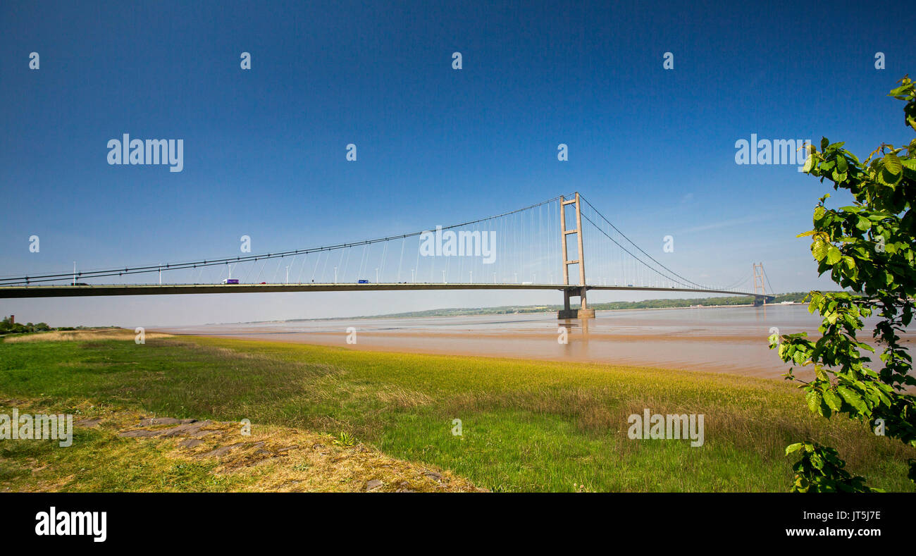 Panoramic view of long suspension bridge over Humber River under blue sky near Kingston Upon Hull, England - Stock Image