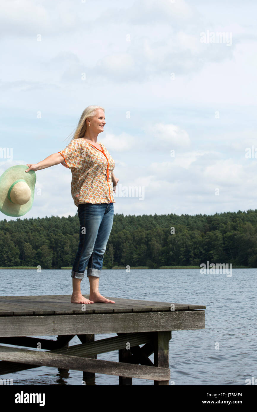 Woman with a straw hat standing on a landing stage - Stock Image