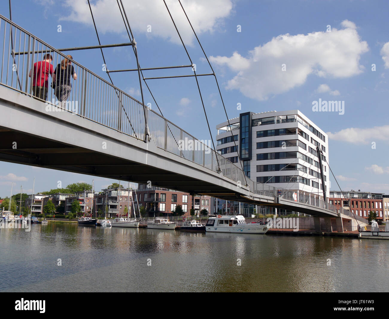 Couple cross the Nesse Bridge in Leer, Germany, The bridge connects the historic city center with the pedestrian zone and crosses the River Leda. - Stock Image