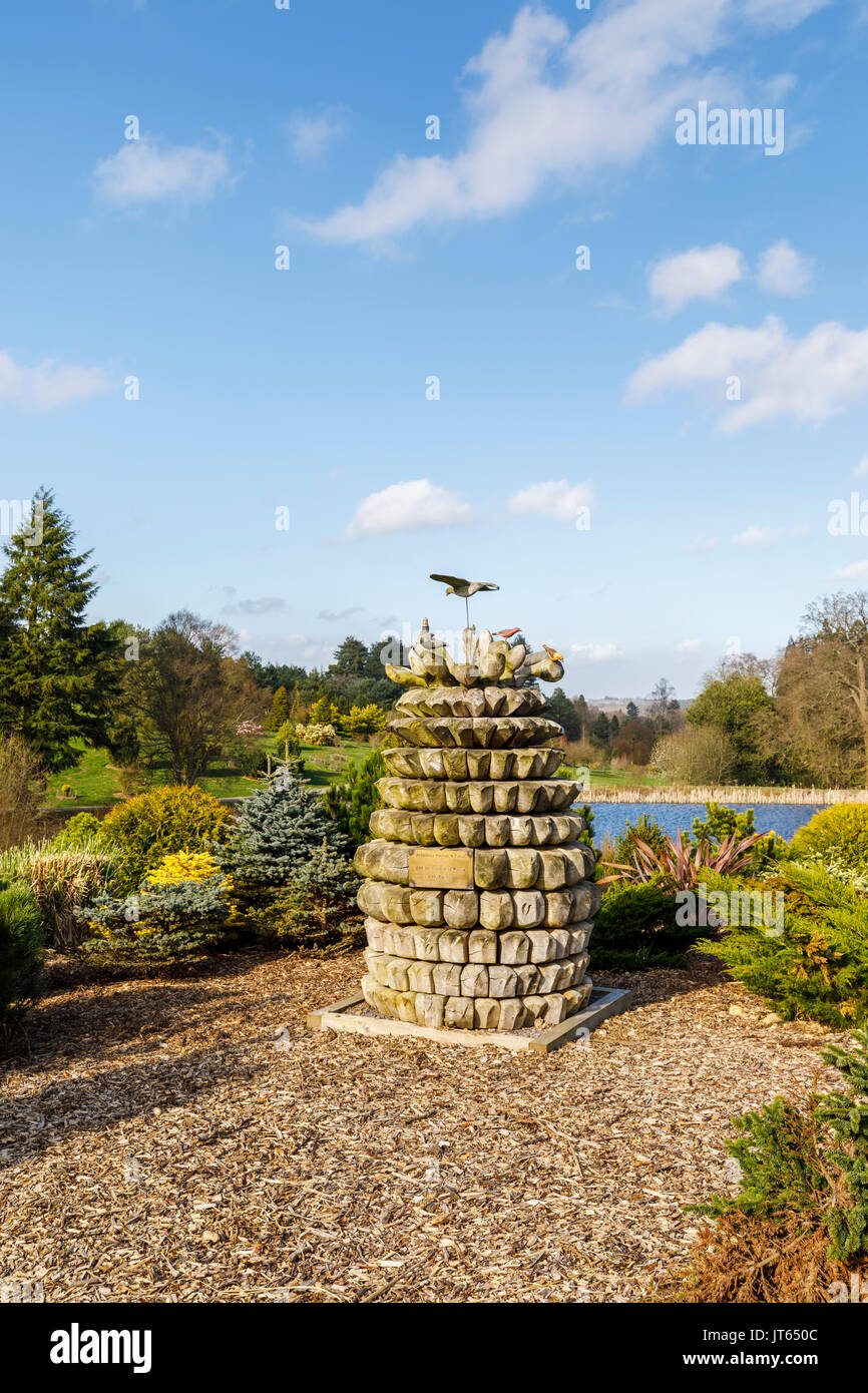Wooden sculpture commemorating the opening of Bedgebury National Pinetum in 2000, Bedgebury, Kent south-east England on a sunny spring day, blue sky - Stock Image