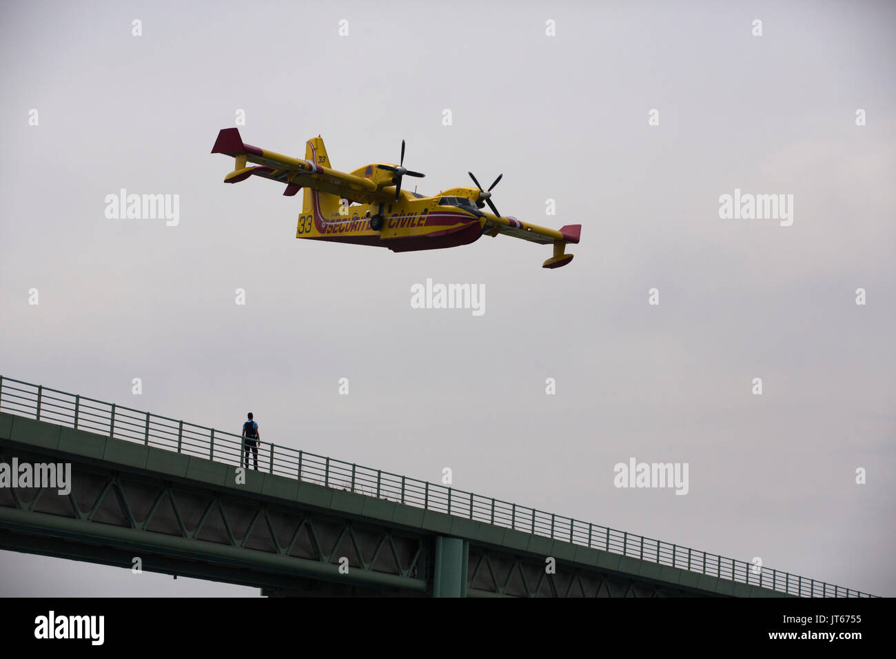 Bathers watch Securite Civile aircarft collecting water at Lac de Saint-Cassien to put out wildfires  in Cote d'Azur, Southern France, Mediterranean - Stock Image