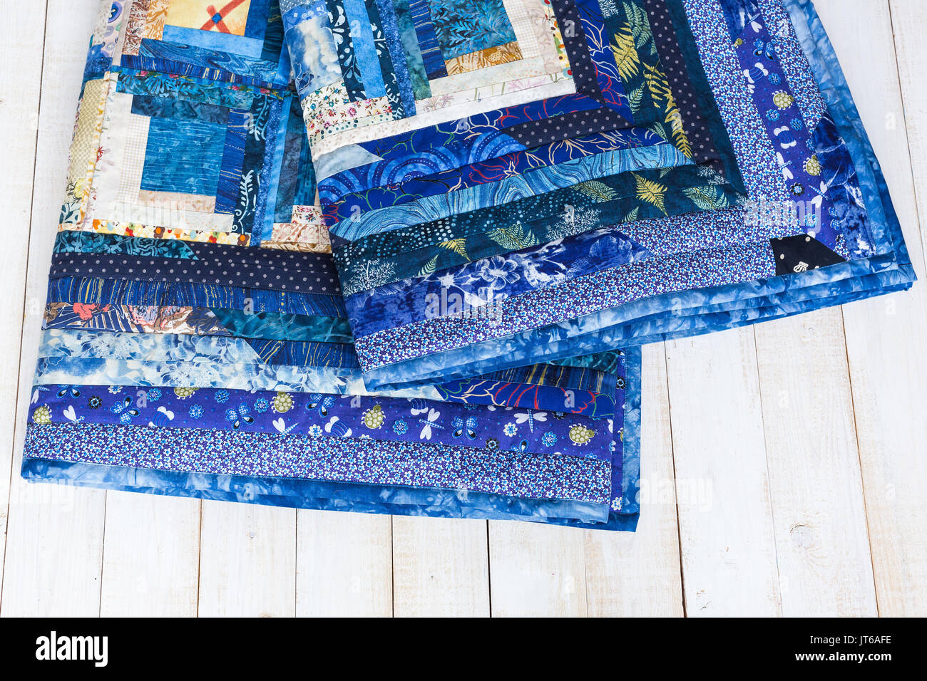 sewing, needlework, geometric, garment industry, cosiness, comfort concept - deep blue colored plaid sewed of textile squares with magnificent print on white wooden boards - Stock Image