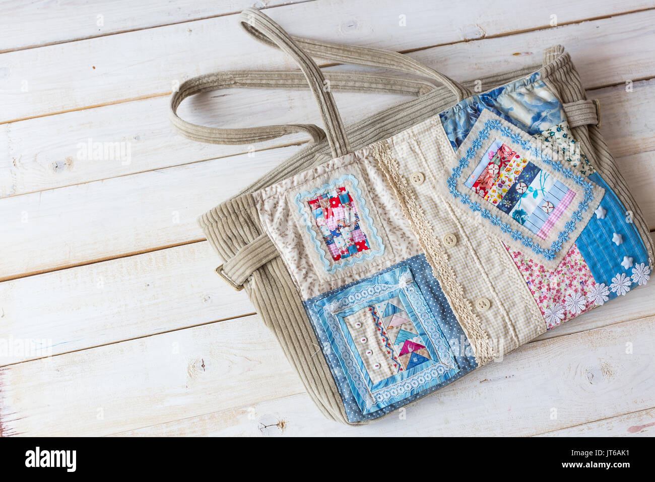 handmade, fashion, accessories concept -flatlay of charming women's bag made of velveteen and front part sewing in technique patchwork with colorful ornate snippets. it has two straps, lace and button Stock Photo