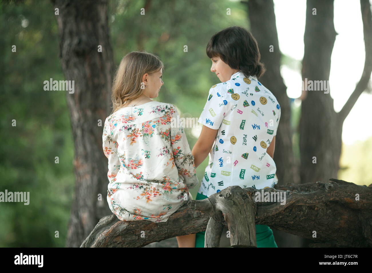 Little Girl And Boy Sit Side By Side On Tree Branch Holding Hands