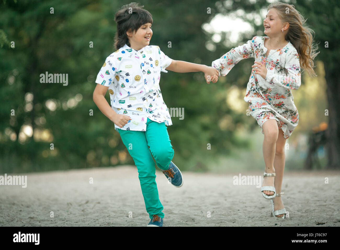 Little Girl And Boy Are Running In Forest Holding Hands Laughing