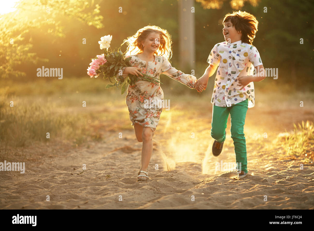Happy Friends Holding Hands And Running In Sunny Stock Photos