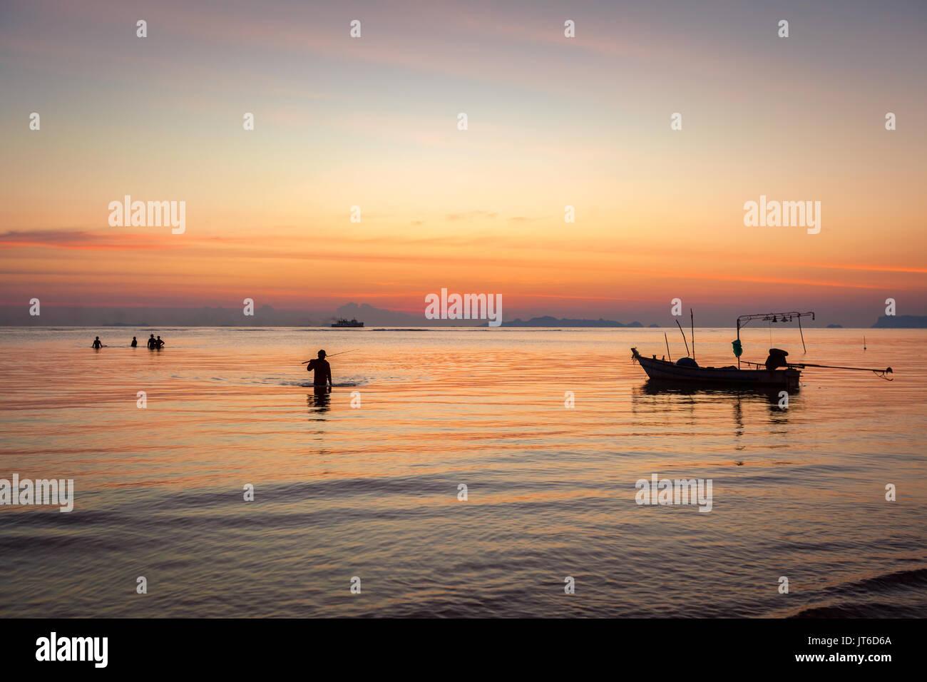 Thai fishermen silhouettes during a colorful tropical sunset, Nathon beach, Laem Yai, Koh Samui, Thailand - Stock Image