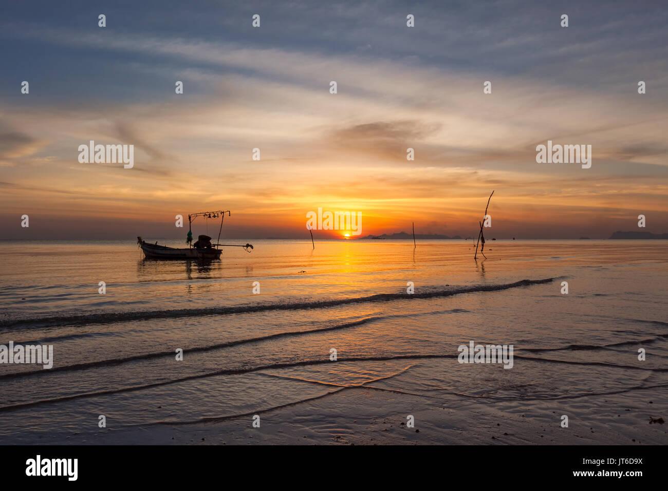 Fishing boat silhouette during a colorful sunset at Nathon beach, Laem Yai, Koh Samui, Thailand - Stock Image