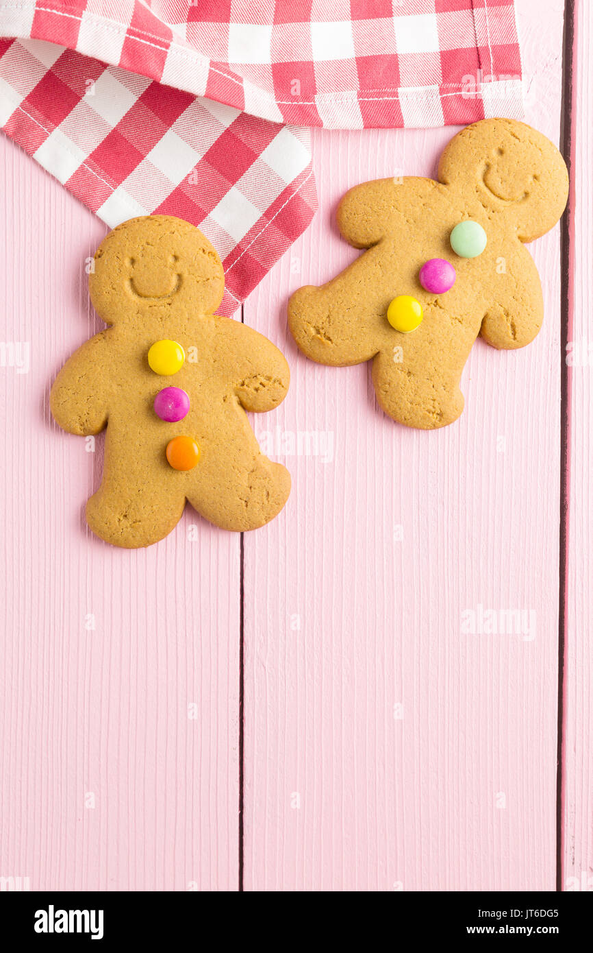 Two gingerbread men on colorful wooden table. Top view. Xmas gingerbread. - Stock Image