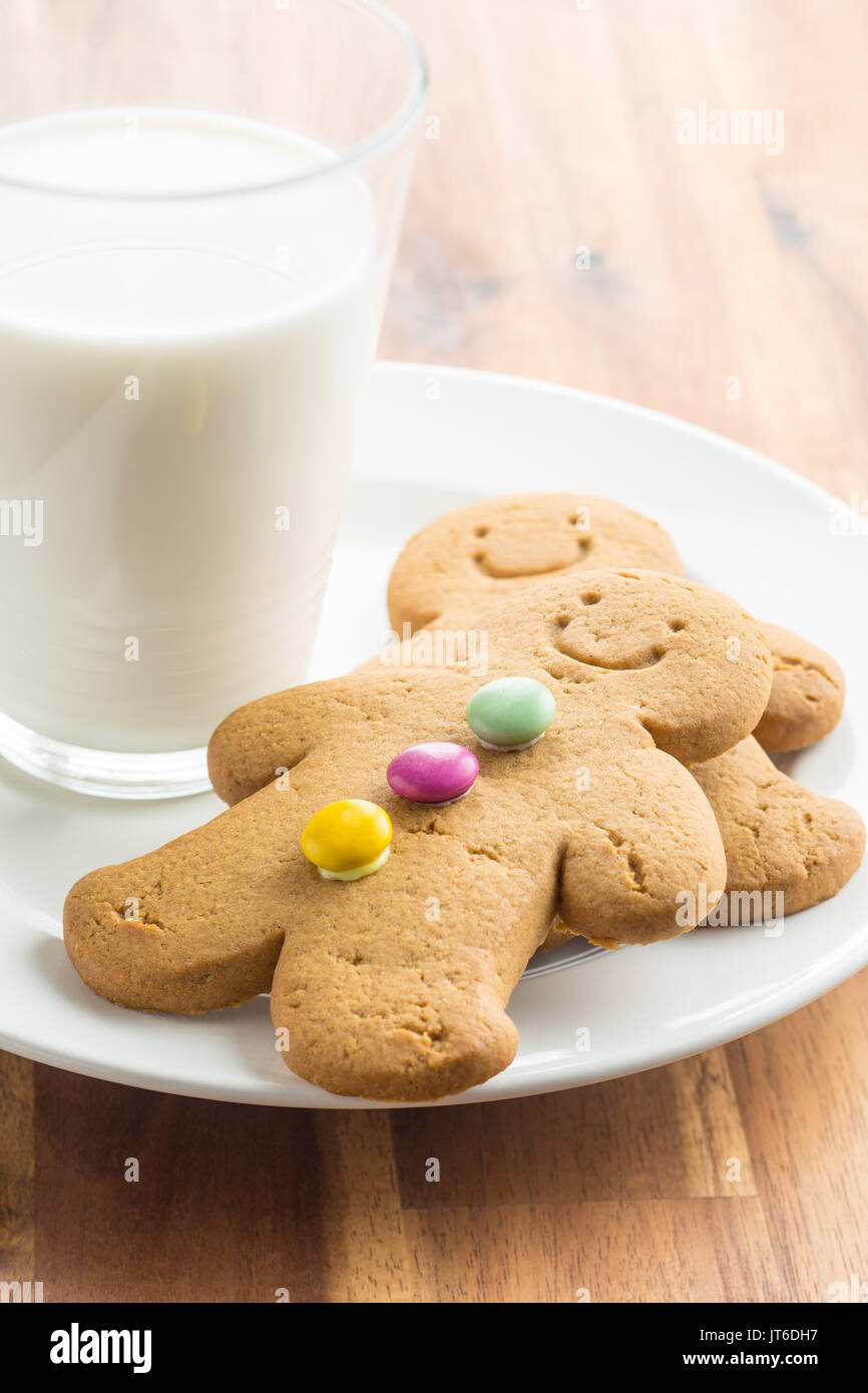 Sweet gingerbread man and glass of milk on wooden table. Xmas gingerbread. - Stock Image