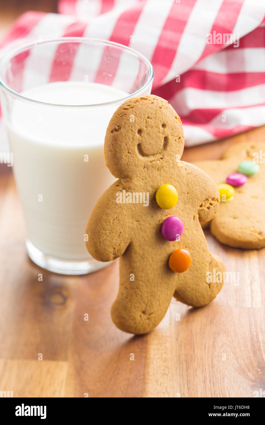 Sweet gingerbread man and glass of milk. Xmas gingerbread on wooden table. - Stock Image