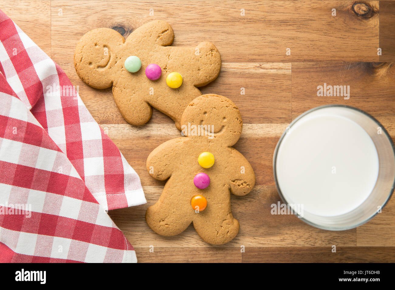 Sweet gingerbread men and glass of milk. Xmas gingerbread on wooden table. - Stock Image