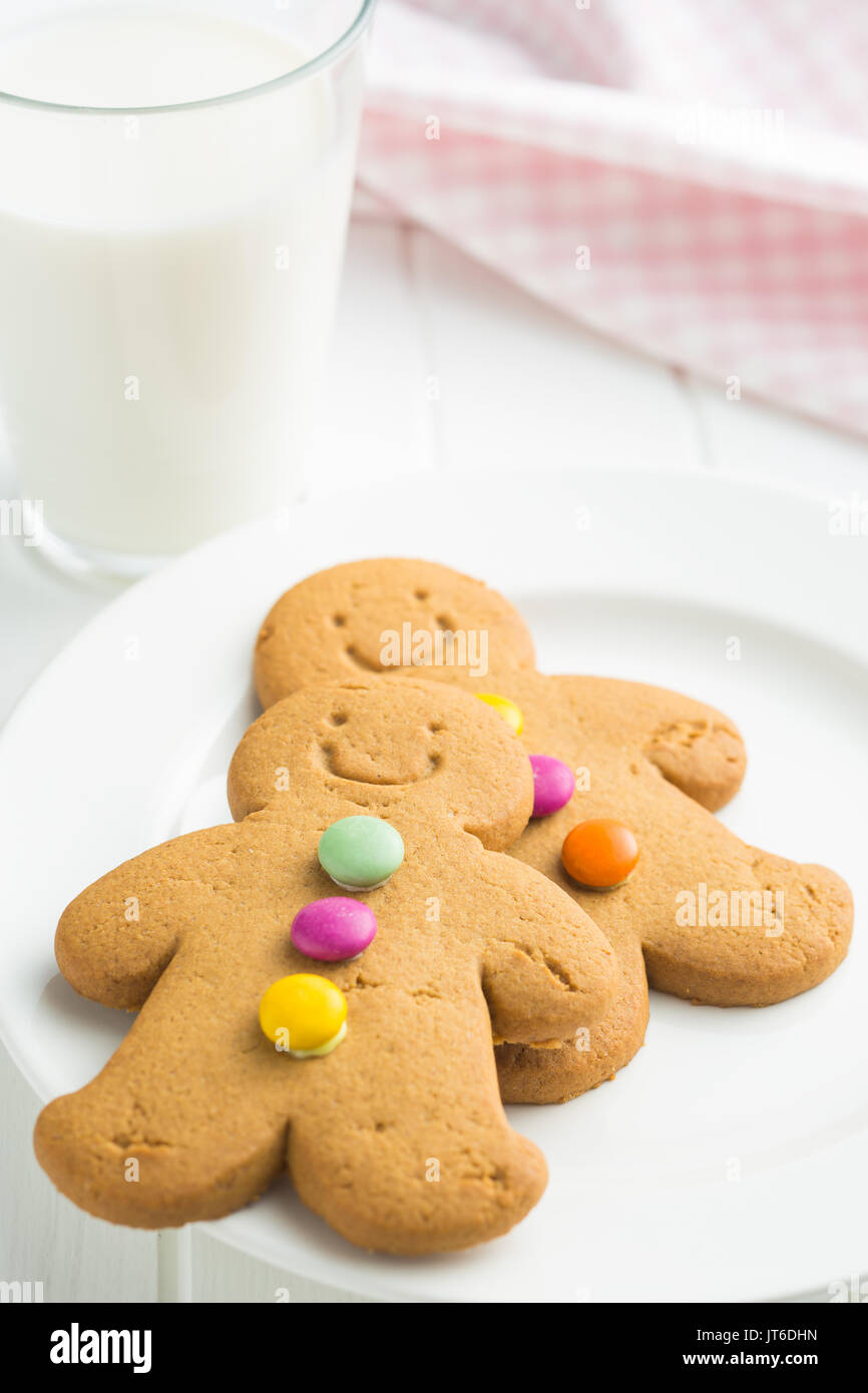 Sweet gingerbread men and glass of milk. Xmas gingerbread on white table. - Stock Image
