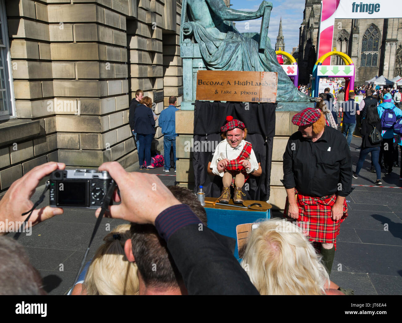 A tourist dressed up as a Scottish Highlander at a photo booth on the Royal Mile, Edinburgh. - Stock Image