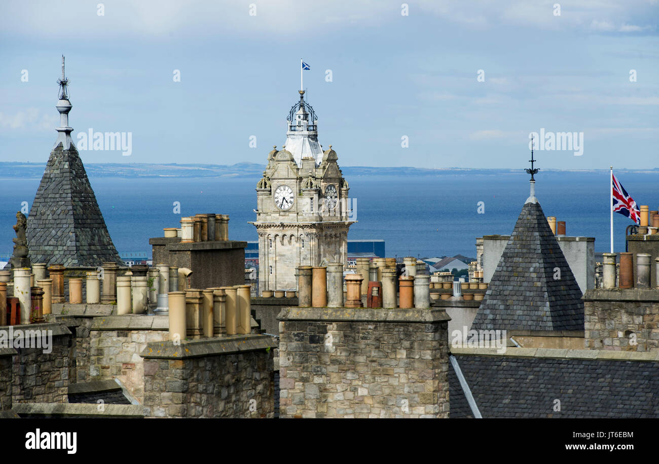 The Balmoral Hotel clock tower framed by the roof tops and chimney pots of Edinburgh's old town. - Stock Image
