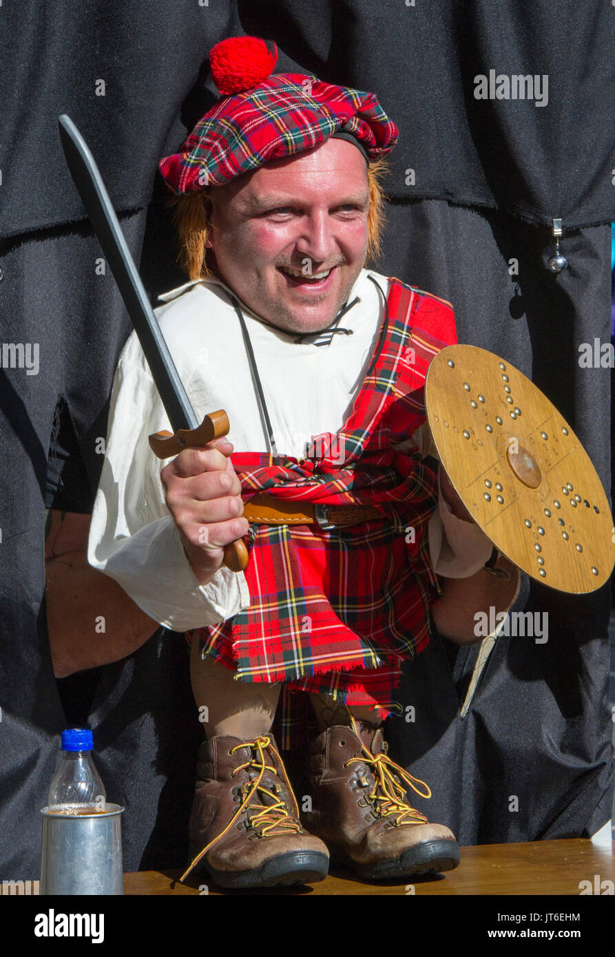 A Tourist Poses As Scottish Highlander At Novelty Stall On The Royal Mile During