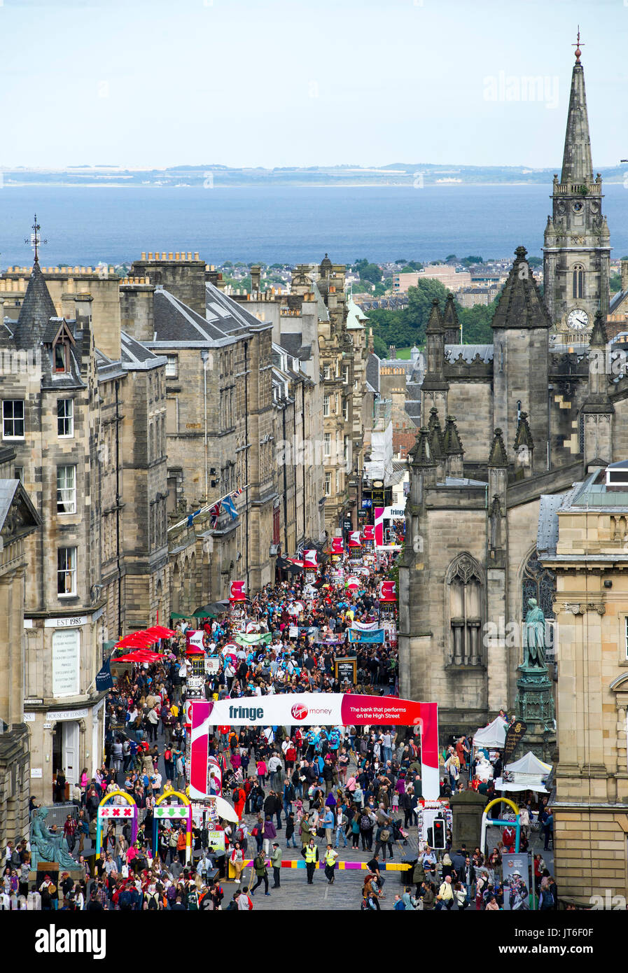 Visitors enjoy the street theatre on the Royal Mile, part of the Edinburgh International Festival Fringe. - Stock Image