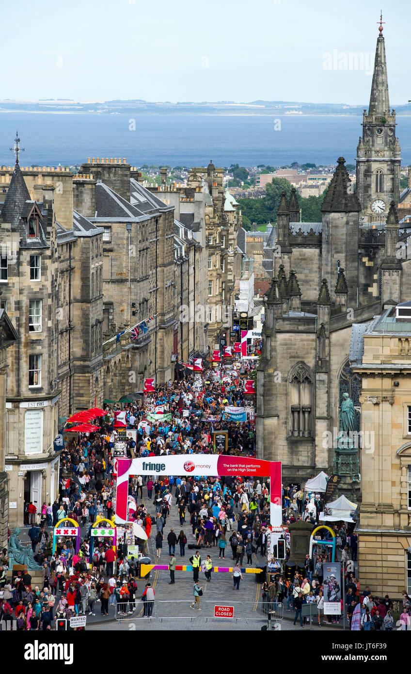 Visitors enjoy the street theatre on the Royal Mile, part of the Edinburgh International Festival Fringe. - Stock Image