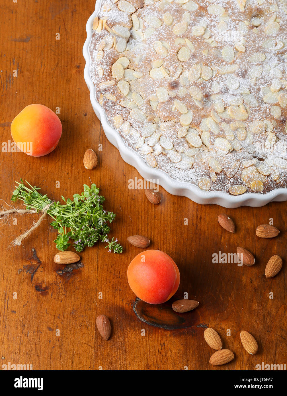 Crustless apricot frangipane tart with almonds and aromatic lemon thyme on rustic brown pine table - Stock Image