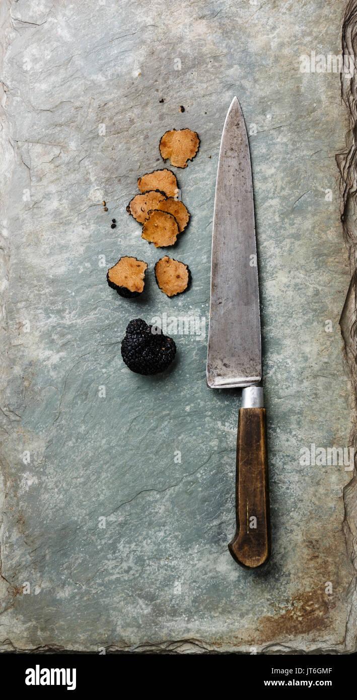 Sliced Black truffle and kitchen knife on stone shale slate background - Stock Image