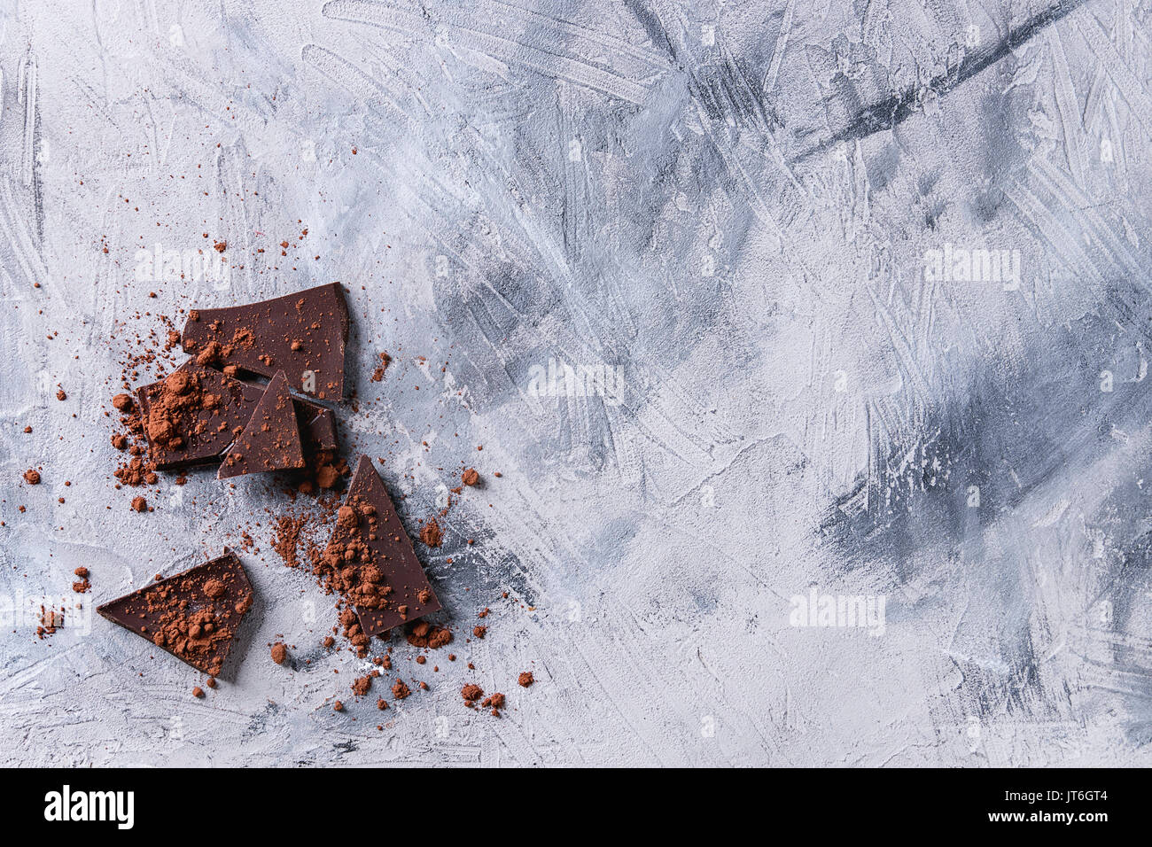 Chopped dark chocolate with cocoa powder over gray concrete texture background. Top view with copy space. - Stock Image