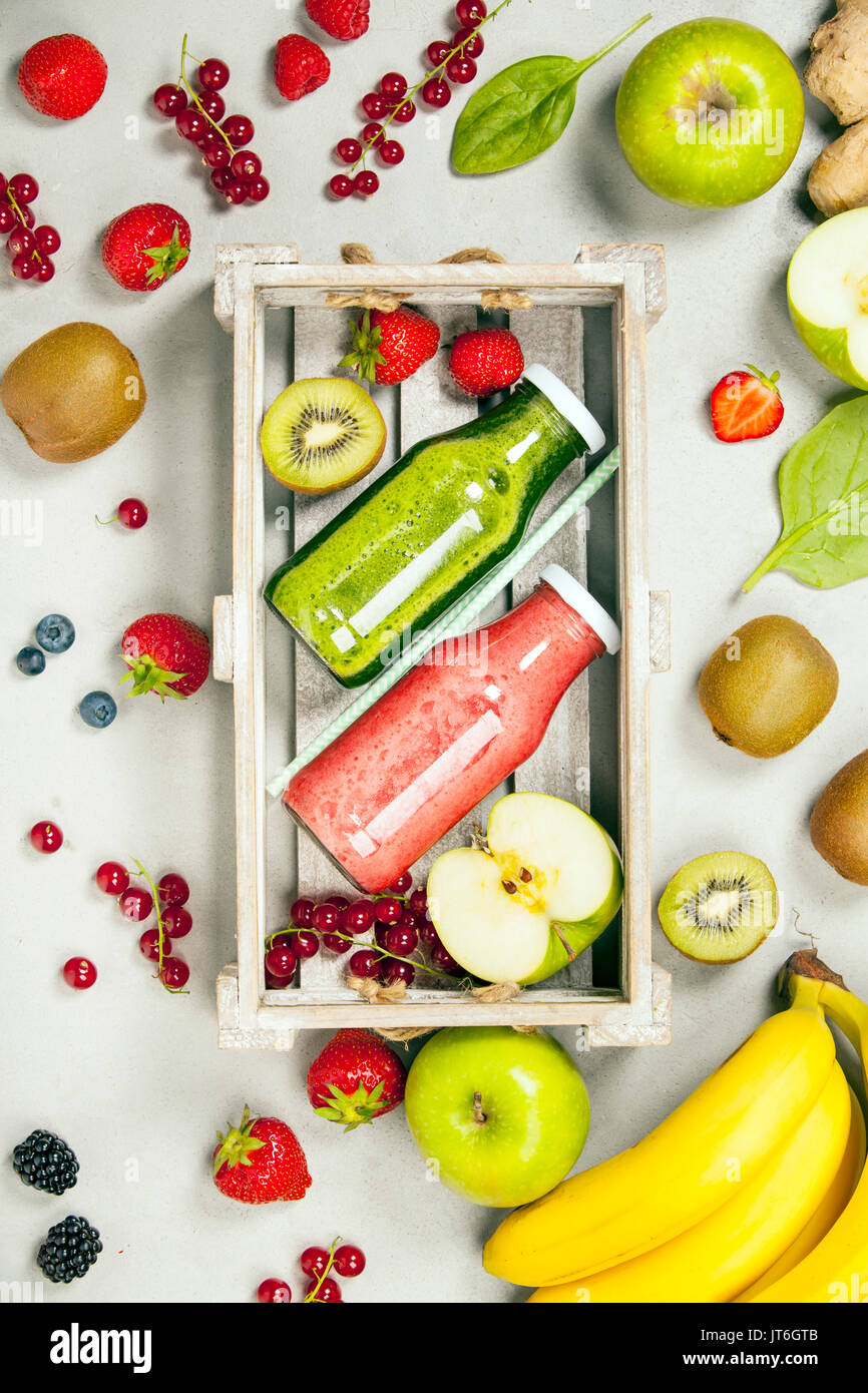 Green and red fresh juices or smoothies with fruit, greens, vegetables on grey background, top view, selective focus. Detox, dieting, clean eating, ve - Stock Image