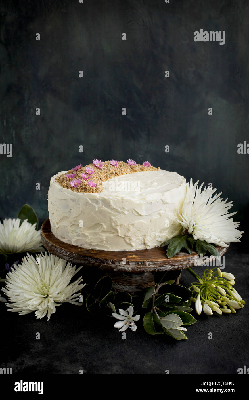 Marzipan Almond Cake with a Orange Blossom Mascarpone Frosting on a wooden pedestal, served with Rosé wine.  Photographed on a black/gray background. - Stock Image