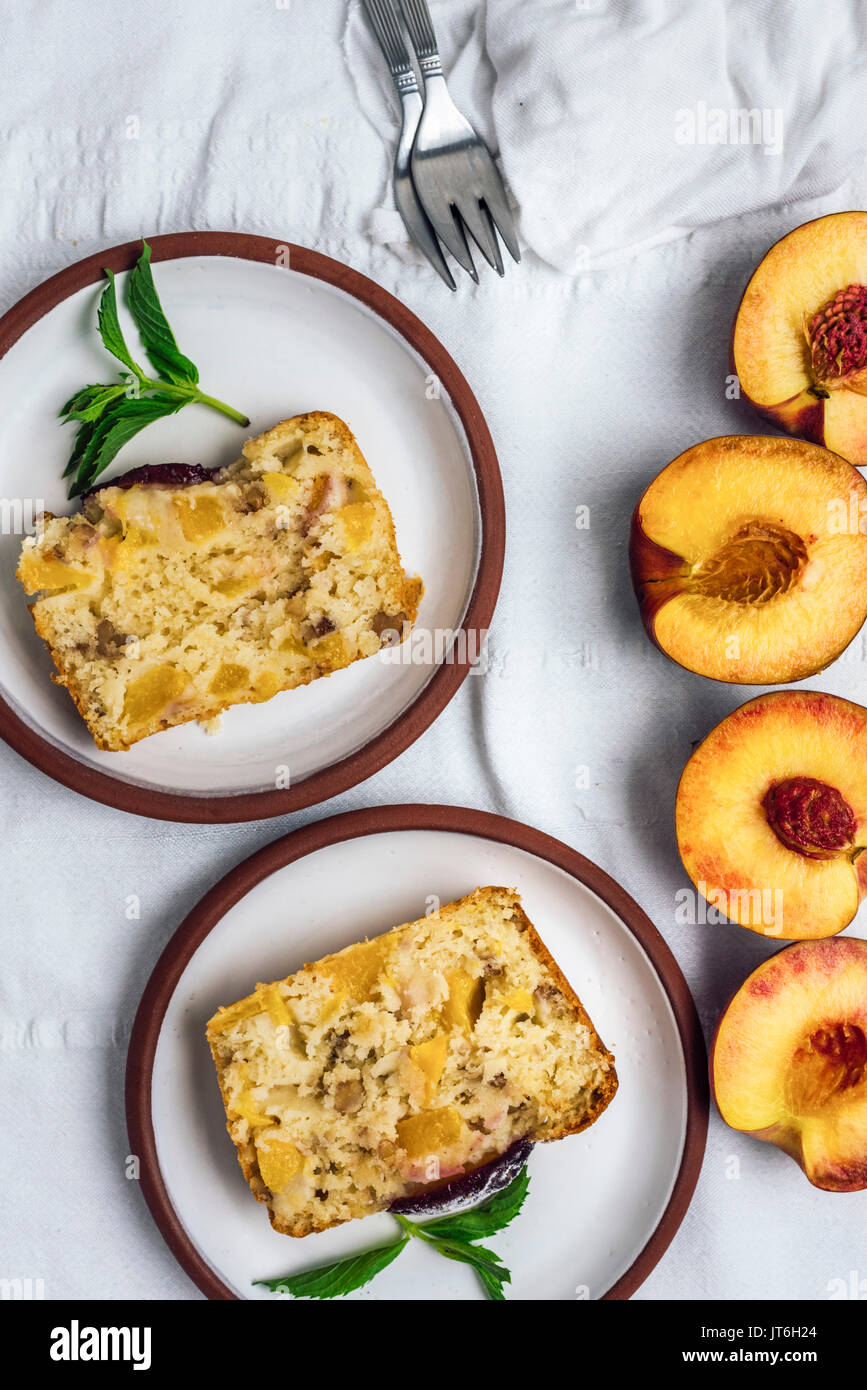Peach bread served on two white plates on a white background accompanied by halved peaches photographed from top view. - Stock Image