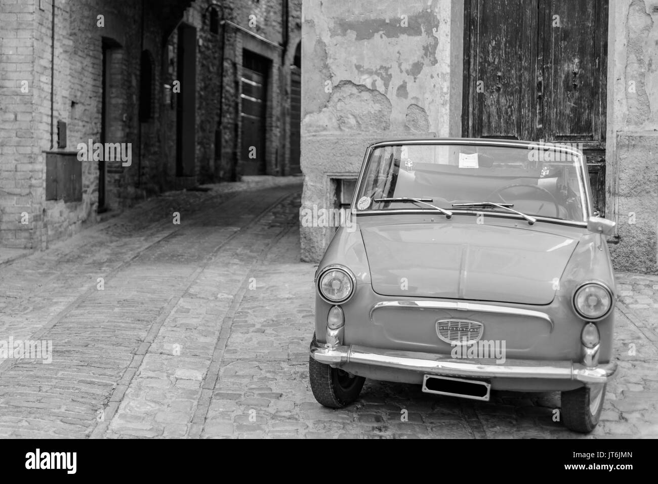 An italian vintage car parked in a street of the historical center of Spello in Umbria - Stock Image