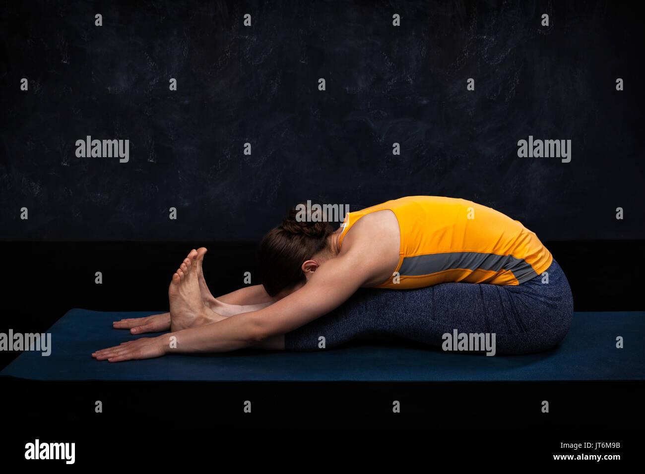 Woman practices Ashtanga Vinyasa yoga asana Paschimottanasana - Stock Image