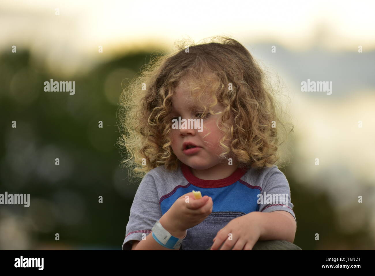 A curly-haired girl eating outside. - Stock Image