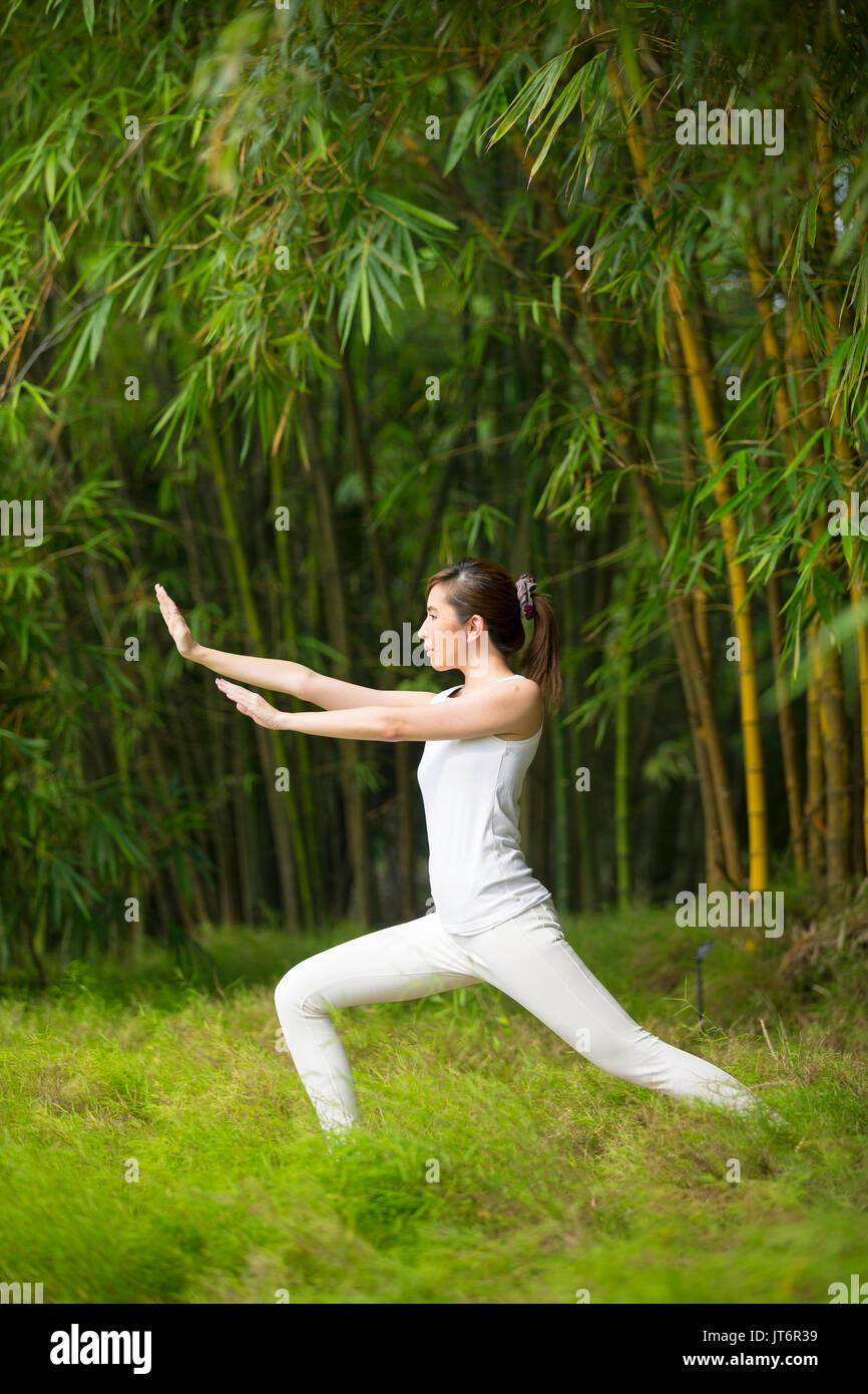 Asian woman practicing Tai Chi in a garden. healthy lifestyle and ...