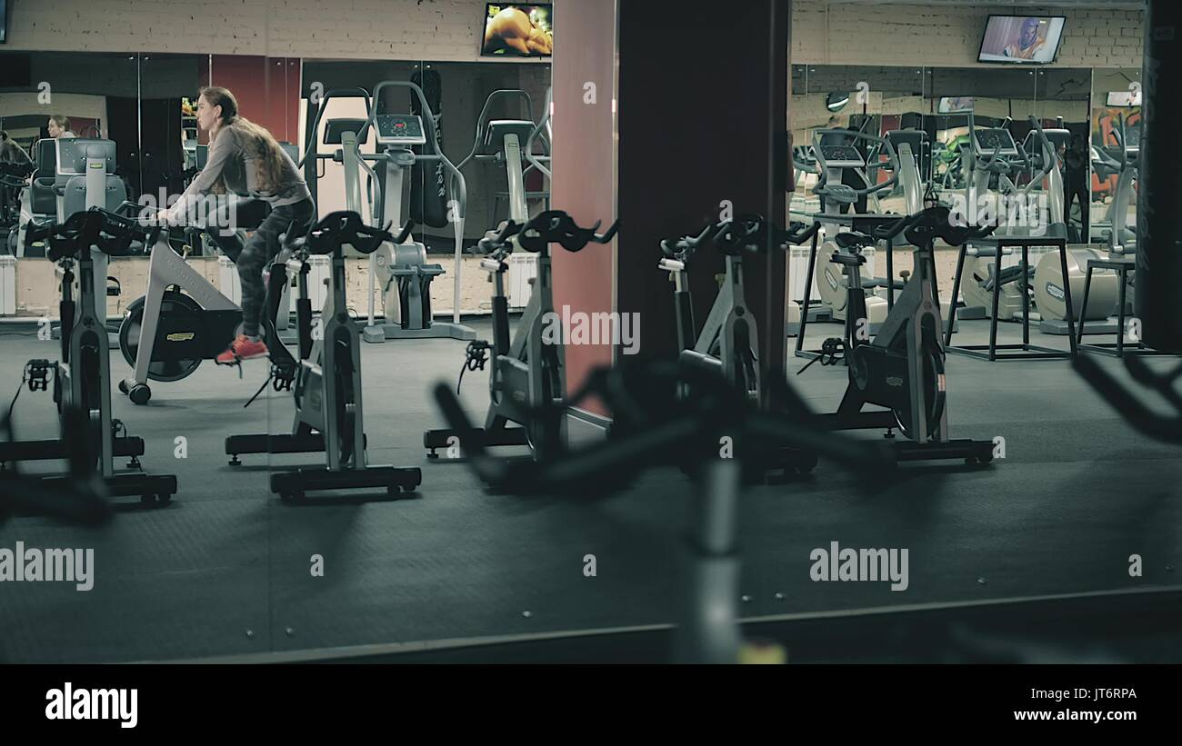 Young beautiful girl in gym, shaking her legs on cycling