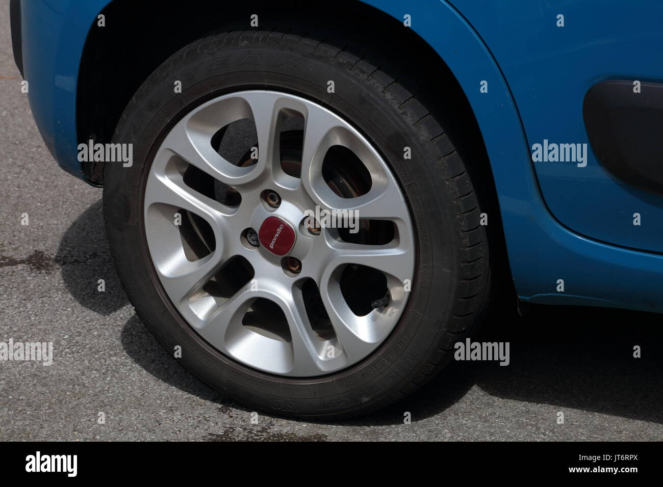 An alloy wheel fixed to a static car with one lock nut and three standard wheel nuts, there is also a car logo disc - Stock Image