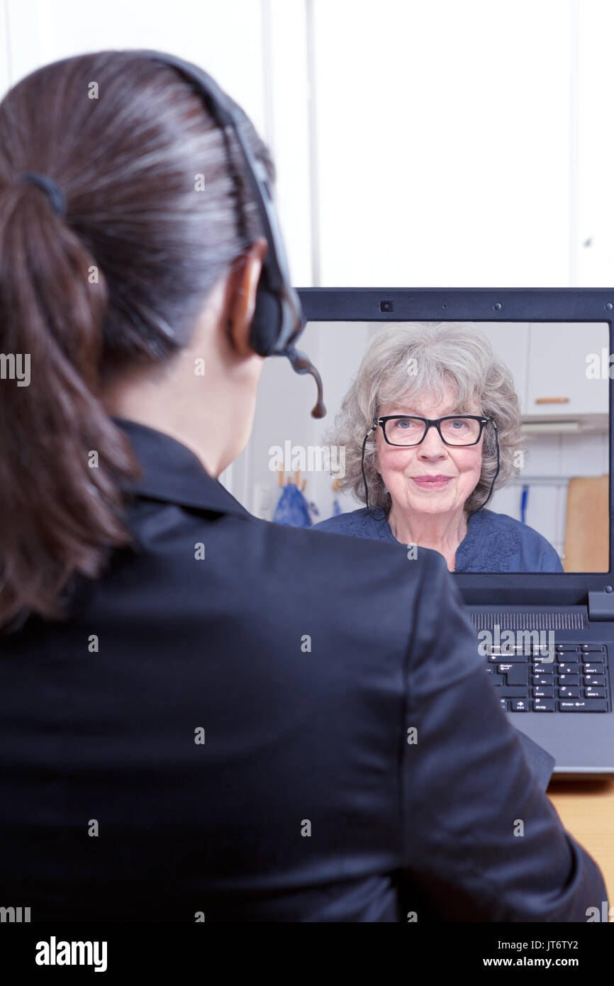 Rear view of a female lawyer or attorney in a black blazer with headset and laptop, having a online video chat with Stock Photo
