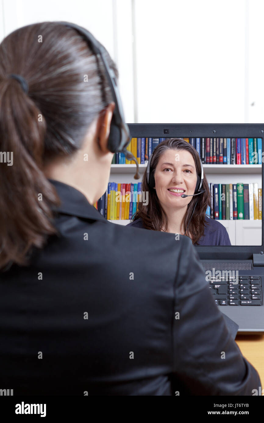 Member of the human resources department in her office with computer and headset, carrying out an online job interview Stock Photo