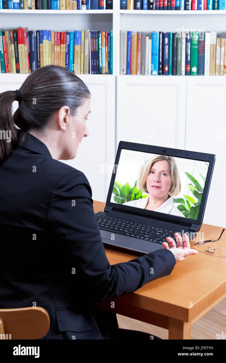 Rear view of a business woman in her office in front of her laptop, having a video call with her physician, telemedicine Stock Photo