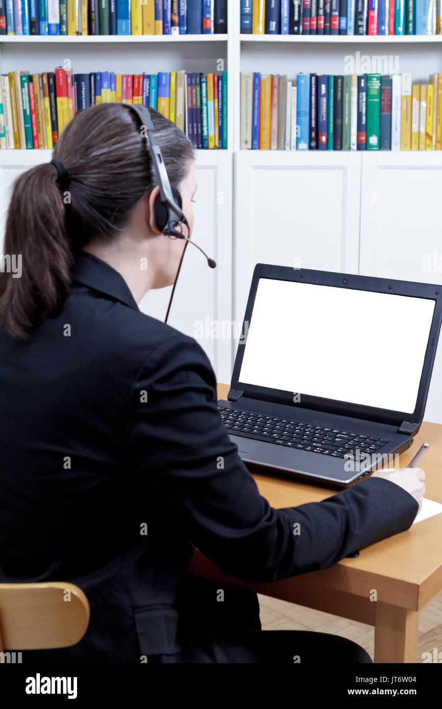 Woman with headset in front of her laptop writing something on a paper while making a live video call, e-therapy Stock Photo