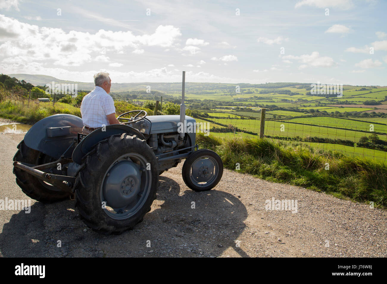 Farmer reminiscing on old tractor looking at farmland landscape - Stock Image