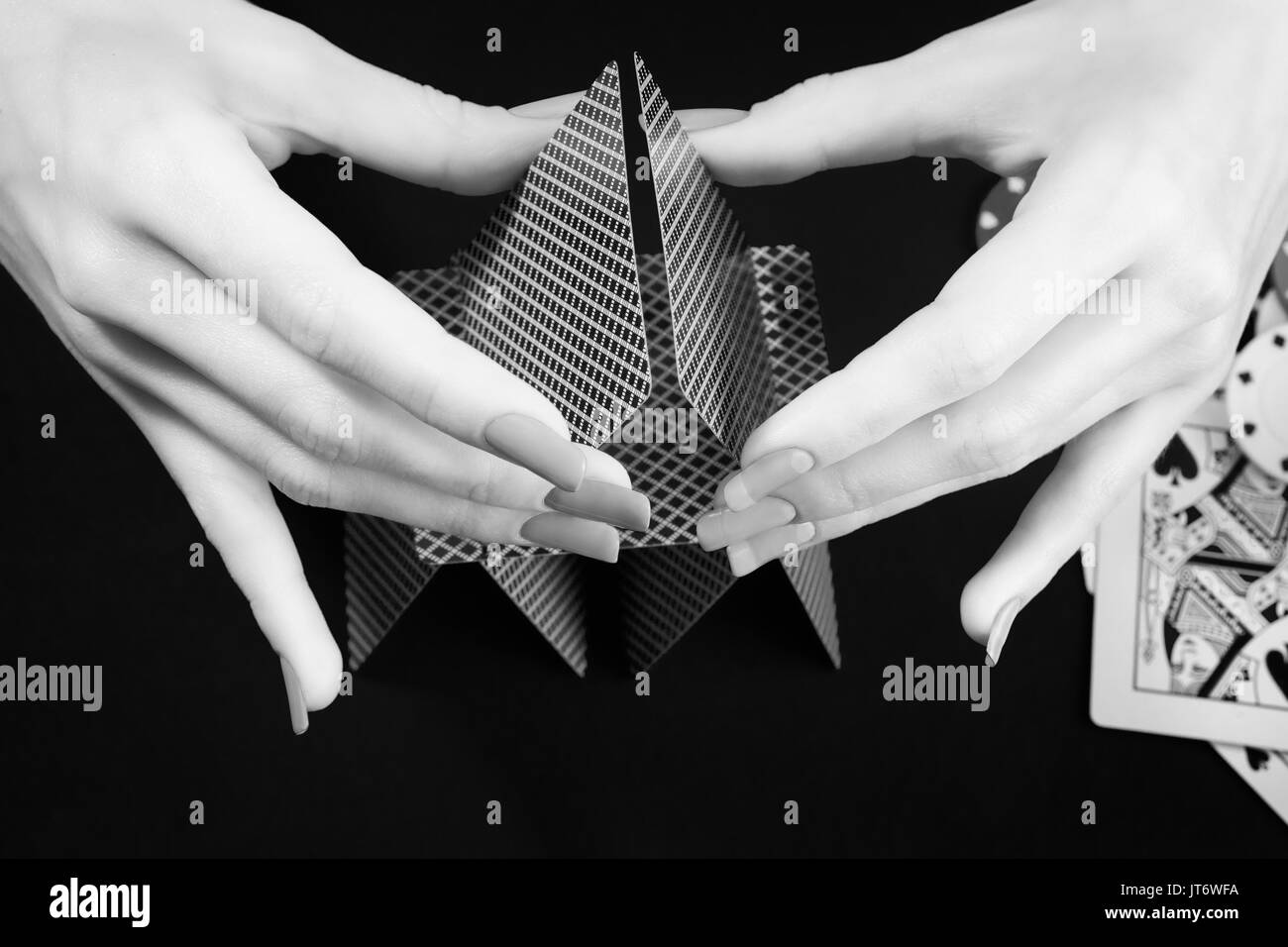 Woman hands assembling house of cards. Black and white photo. Gambling, casino, fortune and chance theme - Stock Image