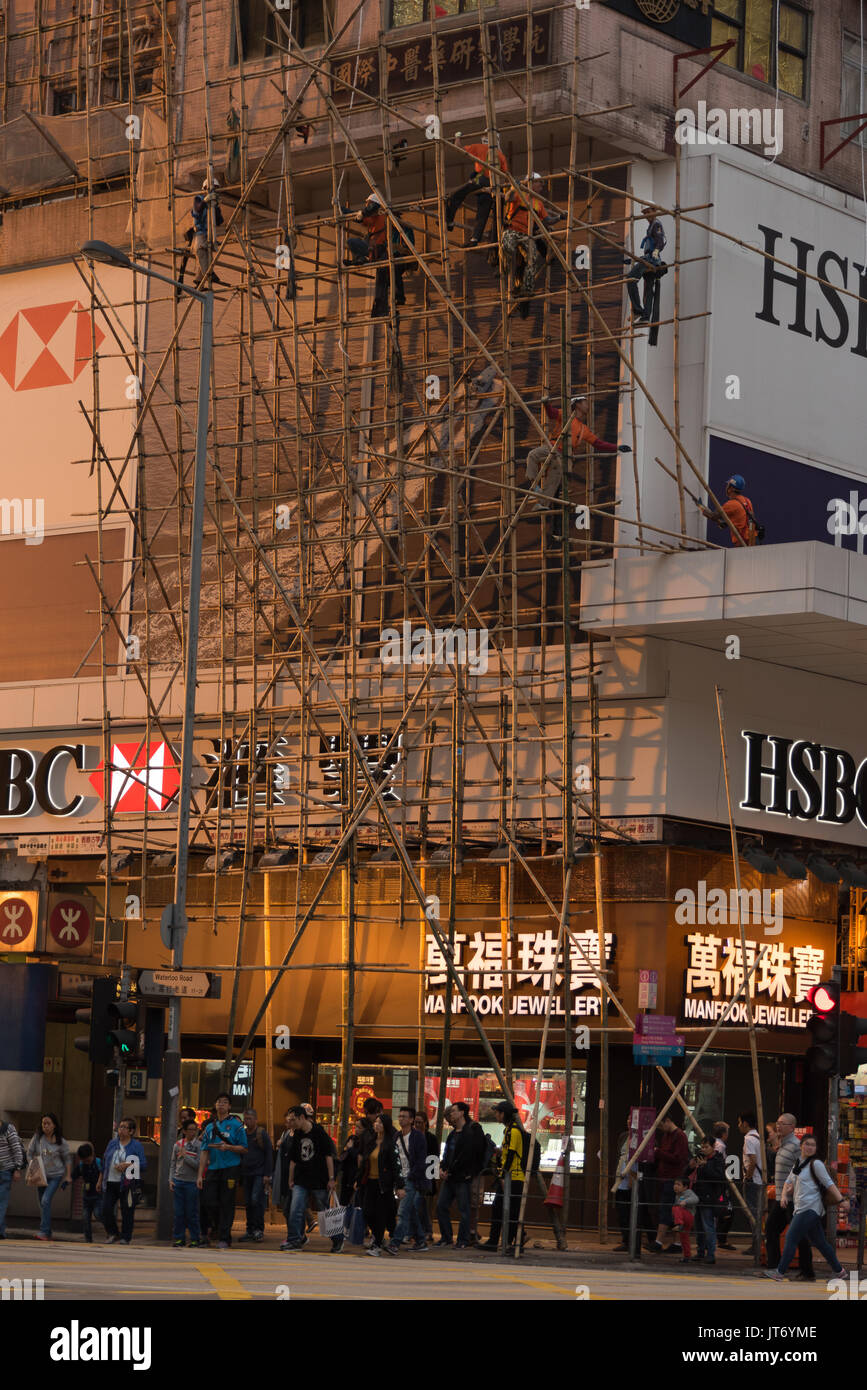 Construction workers build a bamboo scaffolding in the sunset on Nathan Road in Kowloon (Hong Kong) - Stock Image