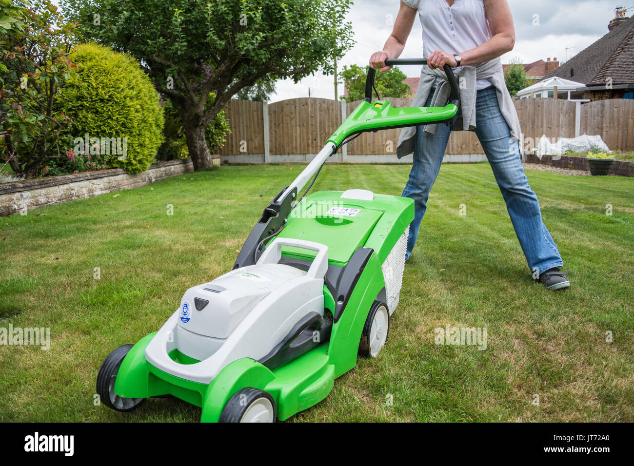 A casually dressed woman mowing the lawn with a VIKING MA339C cordless lawnmower. Candid. Summer, UK. - Stock Image