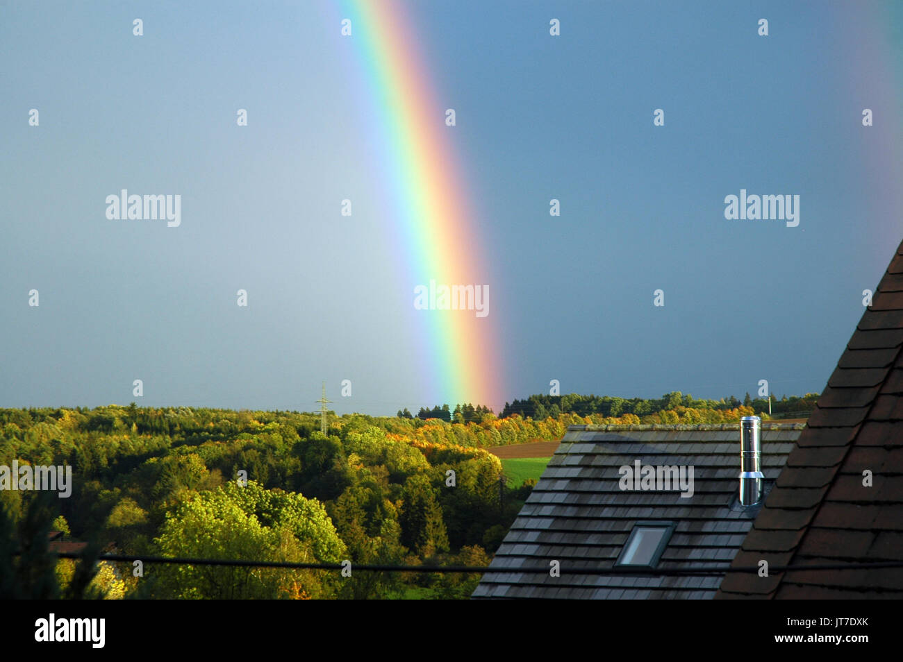 rainbow over forest landscape - Stock Image