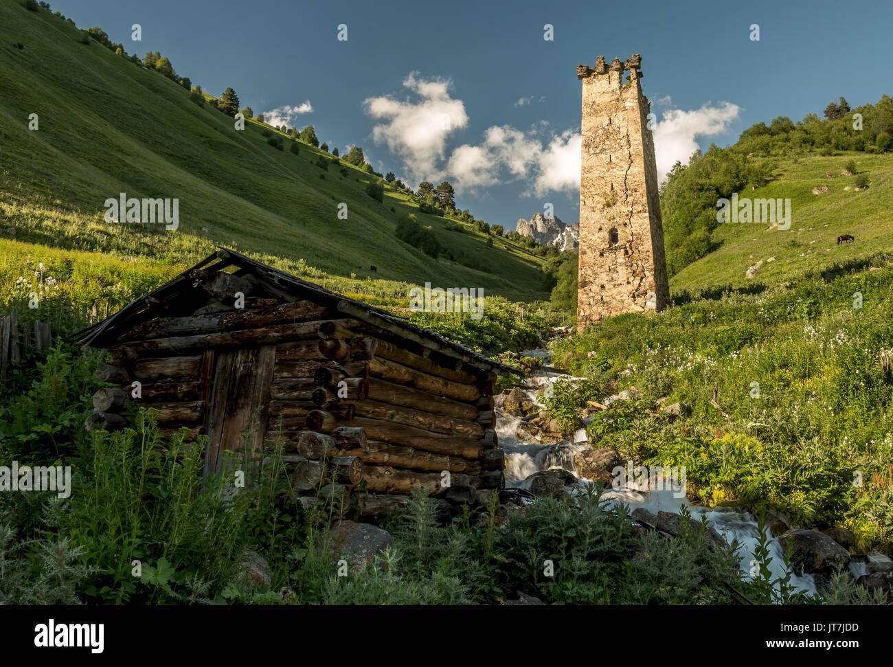 Scenery of Caucasus Svaneti landscape with old medieval defense stone tower, the mountain range, glacial stream, Adishi village, Georgia - Stock Image