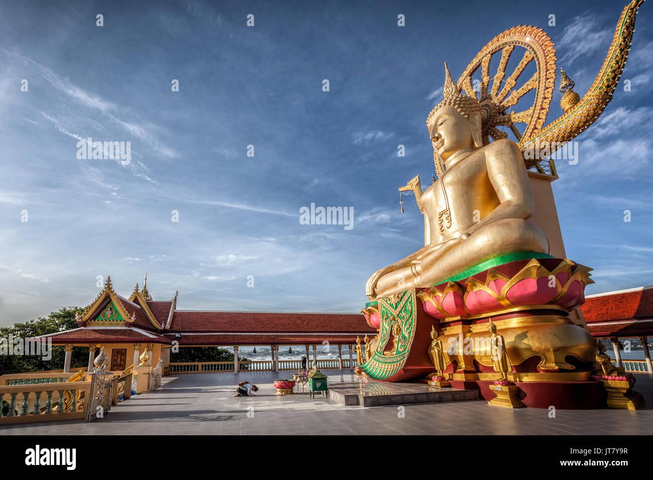 Thai buddhist girl praying in front of Big Buddha, Wat Phra Yai, Kho Samui island, Thailand - Stock Image
