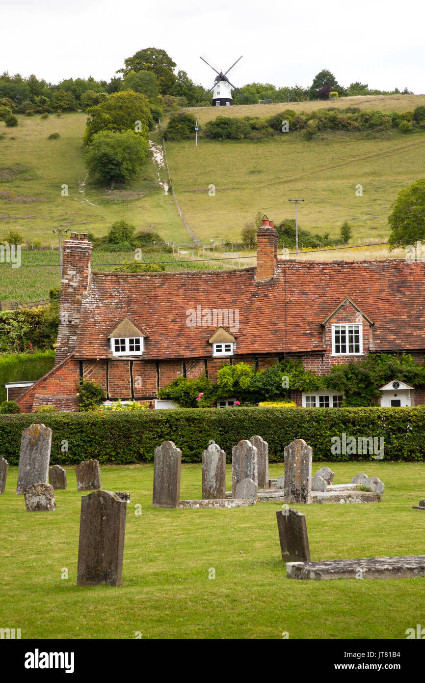 Gravestones in the parish church of St Marys Turville in the English Chiltern hills with a view over country cottages towards Cobstone windmill - Stock Image