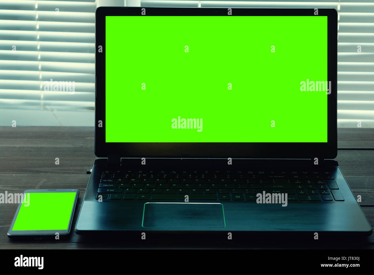 portable computer laptop and smart phone with green screen on a wooden desk. blank display for your presentation. low key shot - Stock Image