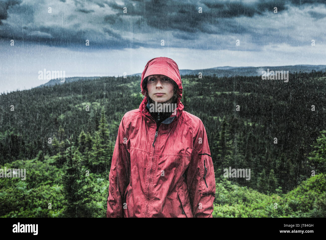 Unpredictable Heavy Rain Pouring on a Sad and Frustrated Young Woman Alone on top of a Mountain. - Stock Image