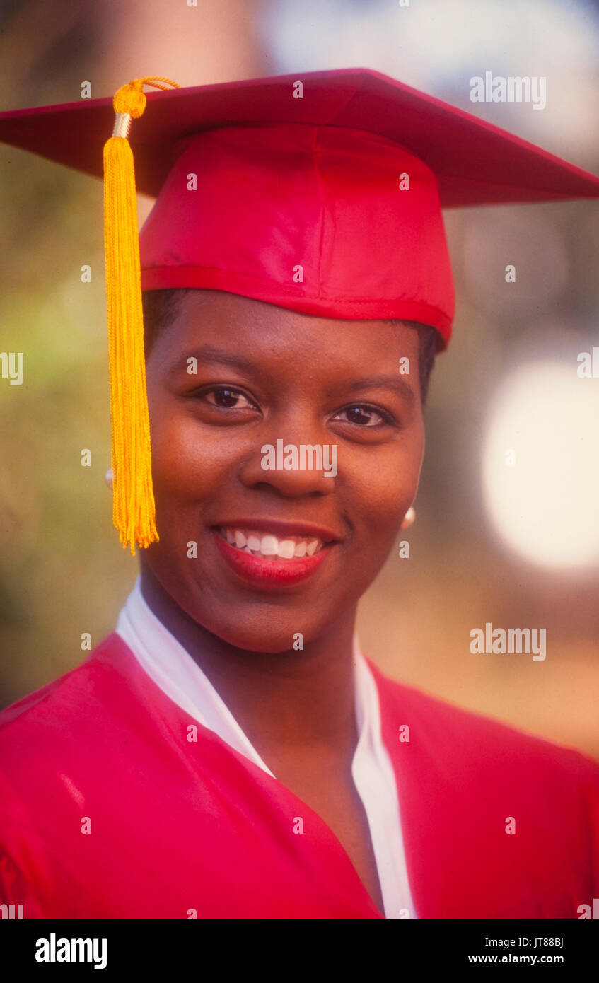 An African American graduate in her red cap and gown with a gold tassel. Stock Photo