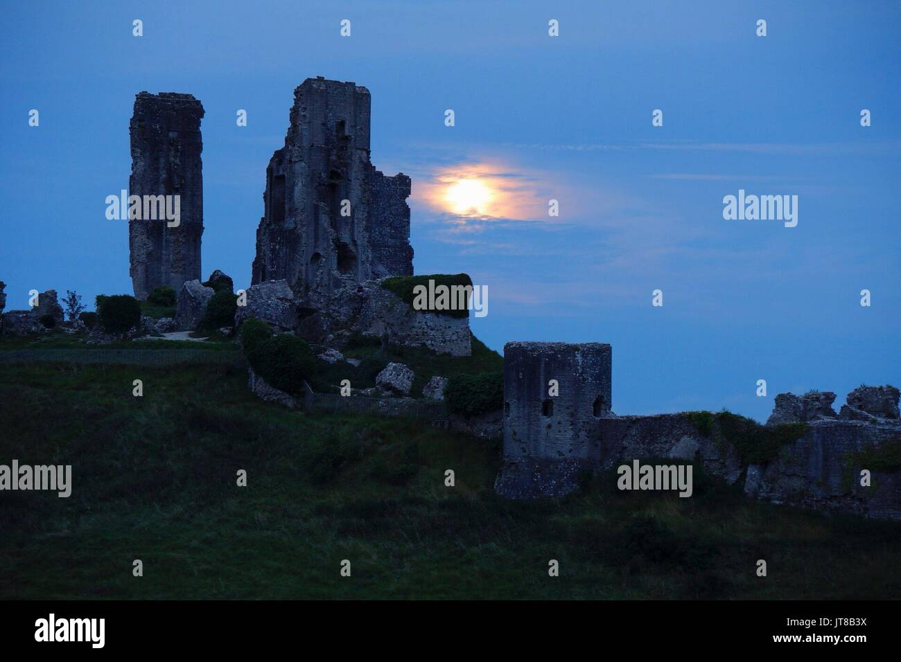 Corfe Castle, Dorset, 7th August 2017. This month sees a full moon appear in hazy conditions over the ancient ruined mount meant in Dorset. Sturgeons moon is so called as it was traditionally known as the easiest time of year to catch Sturgeon fish by night. Credit: Wayne Farrell/Alamy Live News - Stock Image